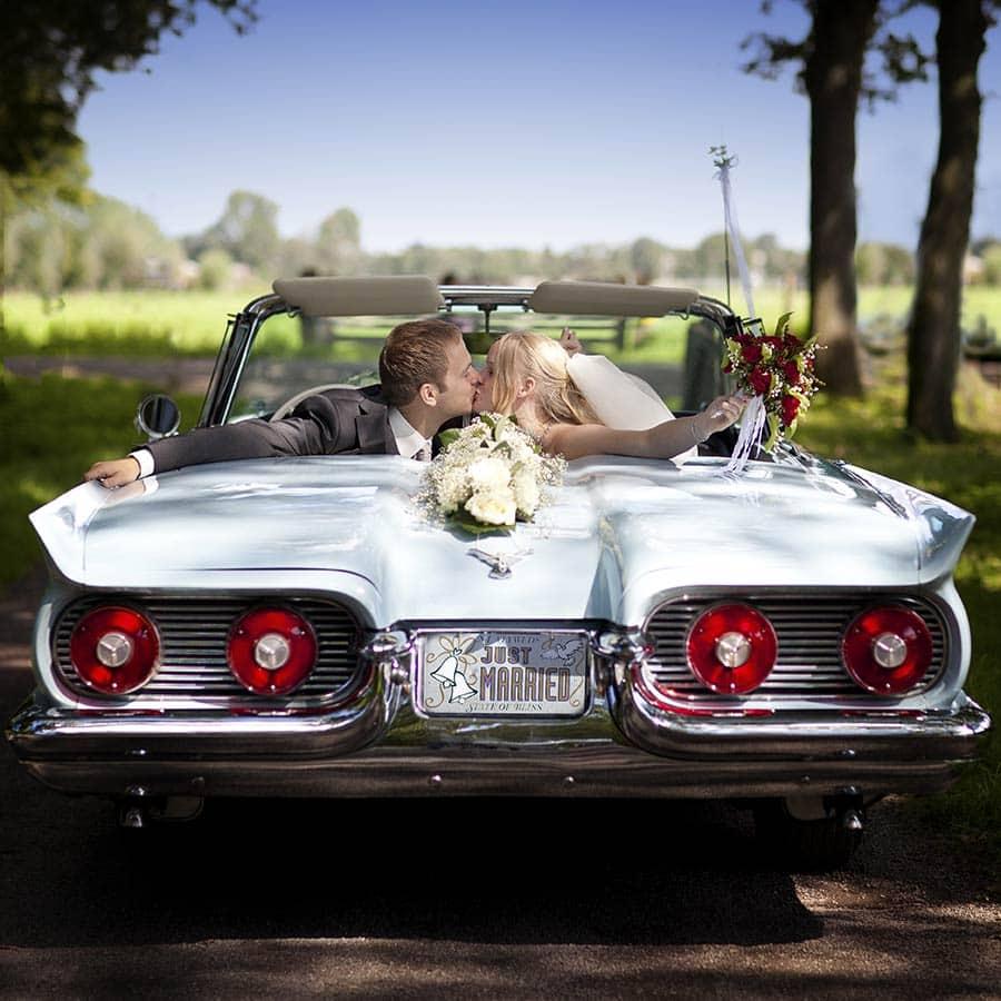 Diverse trouwauto's met bruidspaar