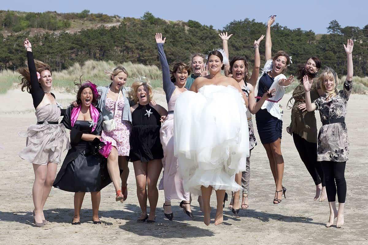 Bruid & vriendinnen springen op het strand
