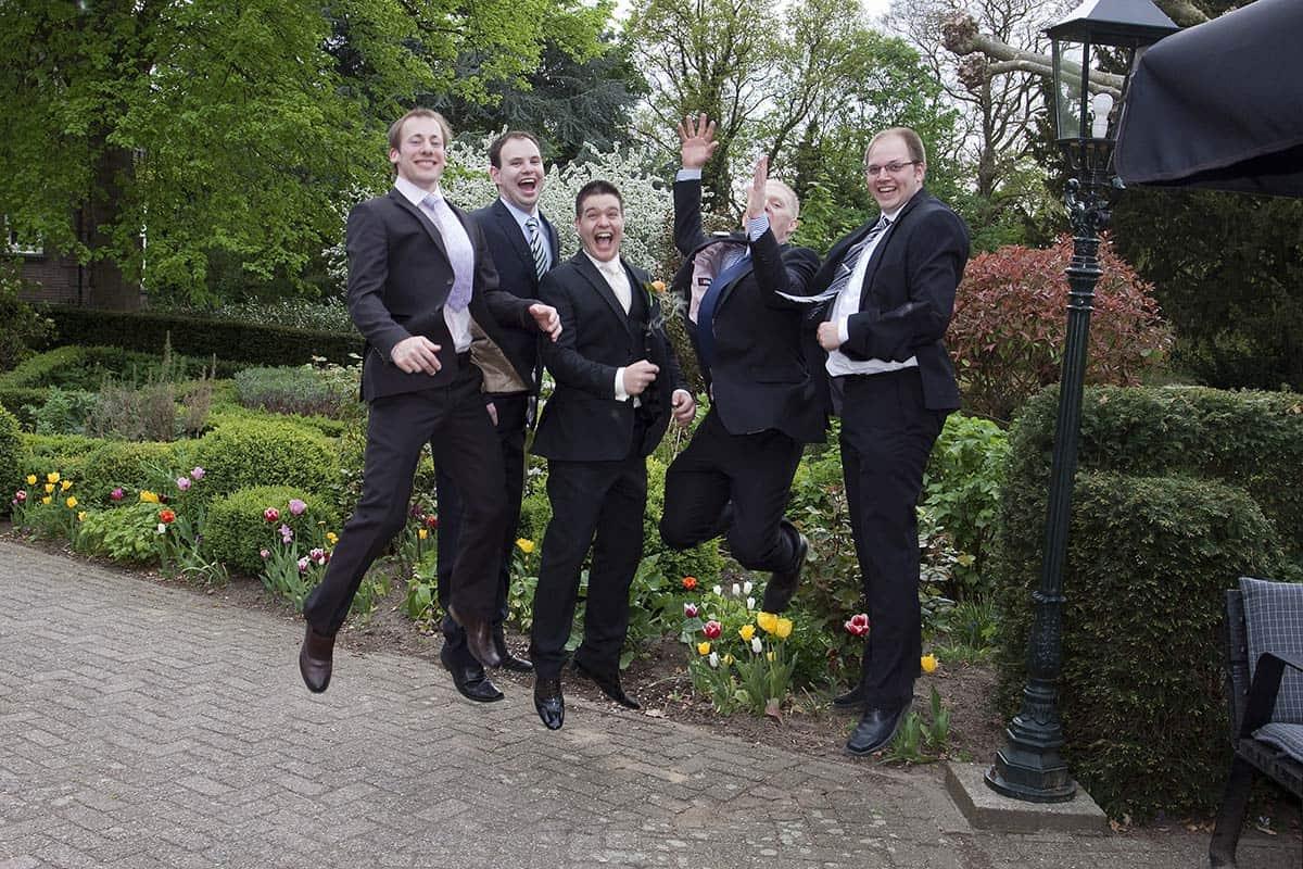 bruidegom vrienden familiefoto's bruiloft trouwdag springen trouwen