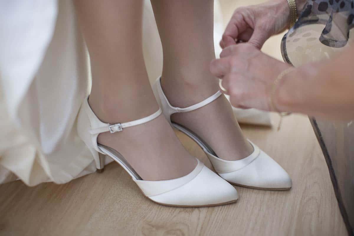 Trouwfoto trouwschoenen aantrekken bruid bruidsfotografie bruidsfoto