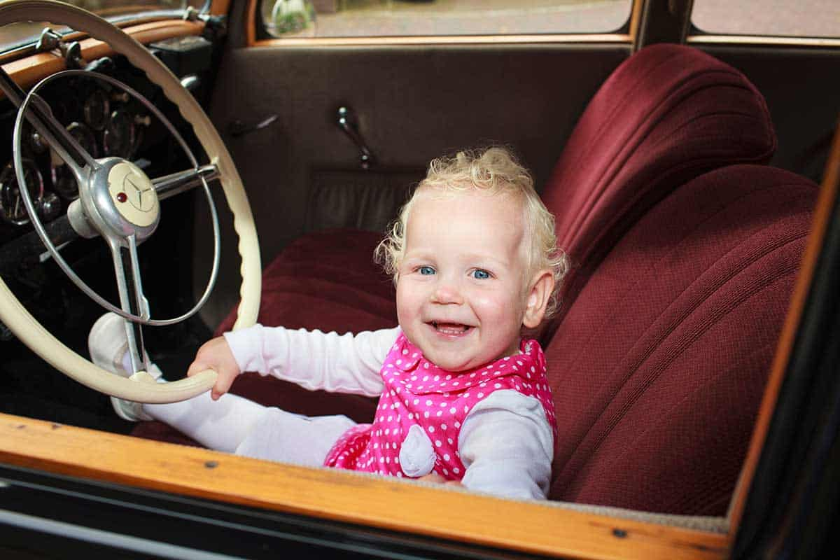 baby achter het stuur trouwauto trouwdag trouwen bruidskinderen portret