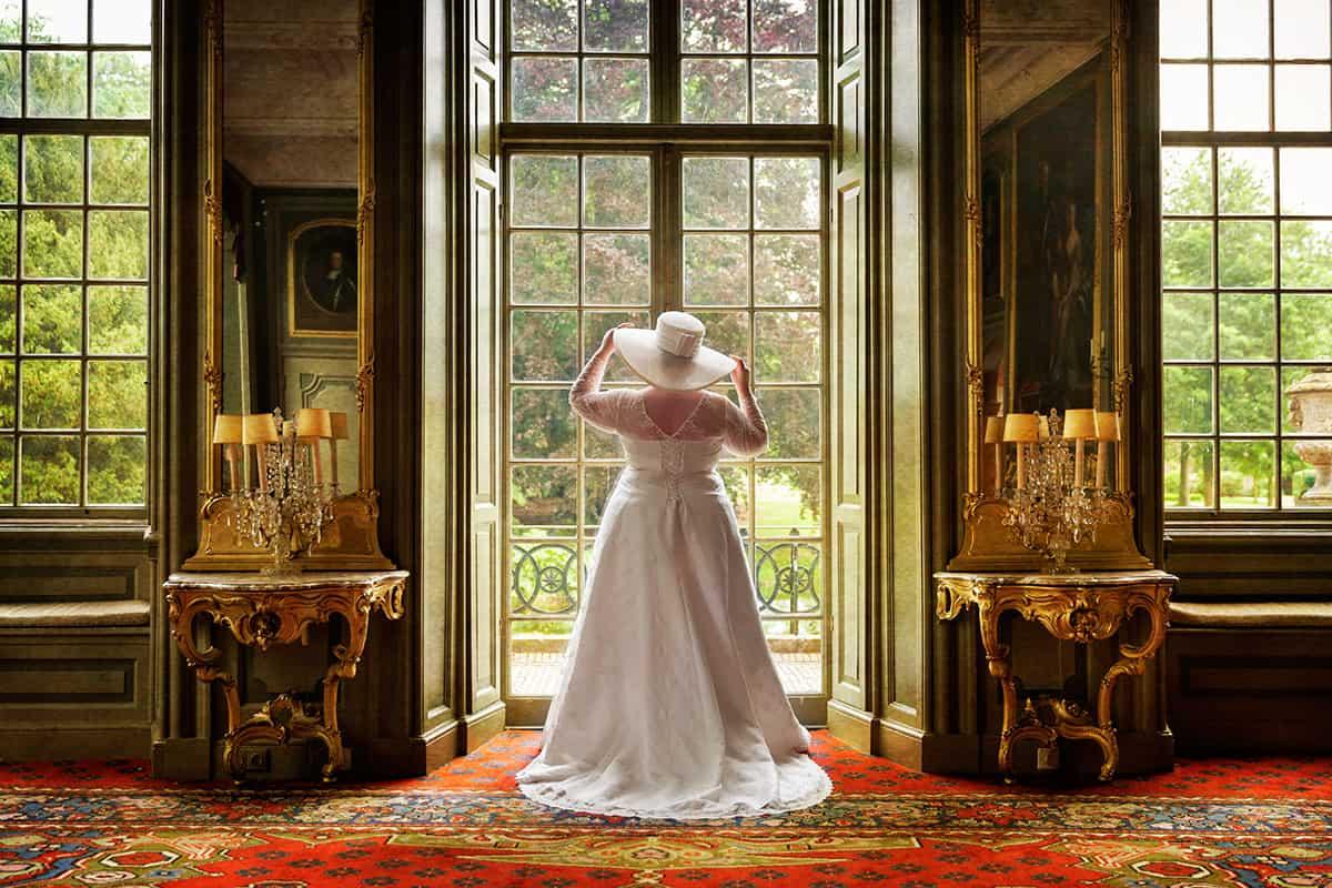 bruid met hoed bij raam